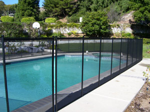 All-Safe® DIY black mesh swimming pool fence installed around a swimming pool